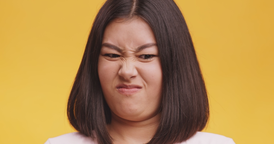 Disgusting odour. Discontent asian woman frowning face, smells something awful, feeling aversion, orange studio background   Shutterstock HD Video #1062897664