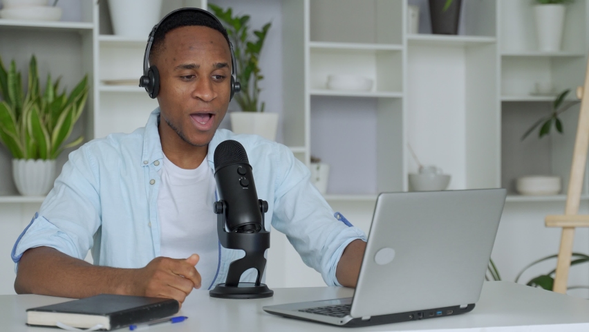 Podcast concept - happy young black man audio blogger in headphones with laptop computer and microphone broadcasting at home office Royalty-Free Stock Footage #1062900454