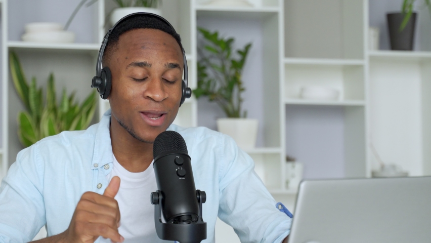 Podcast concept - happy young black man audio blogger in headphones with laptop computer and microphone broadcasting at home office Royalty-Free Stock Footage #1062900463