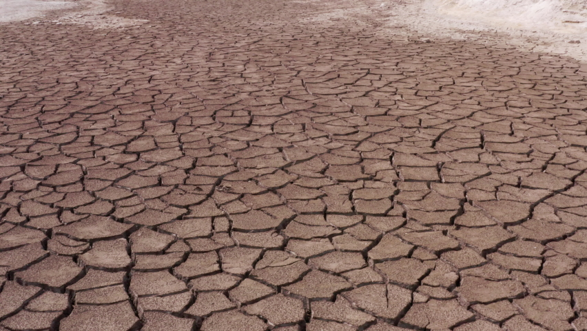 A view of a cracked surface of a parched lake. The concept of global warming, environmental pollution and post-apocalypse | Shutterstock HD Video #1062910924