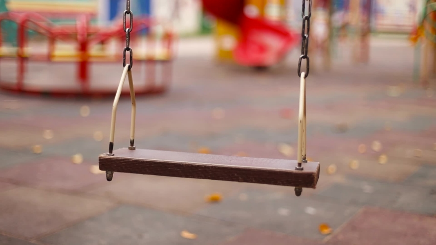 Empty wooden swing with metal chains on the playground in city park. Without children and people during the coronavirus pandemic. | Shutterstock HD Video #1062912205