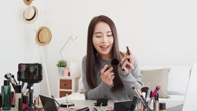 Young beautiful Asian woman professional beauty vlogger doing cosmetic makeup tutorial online live streaming at home
