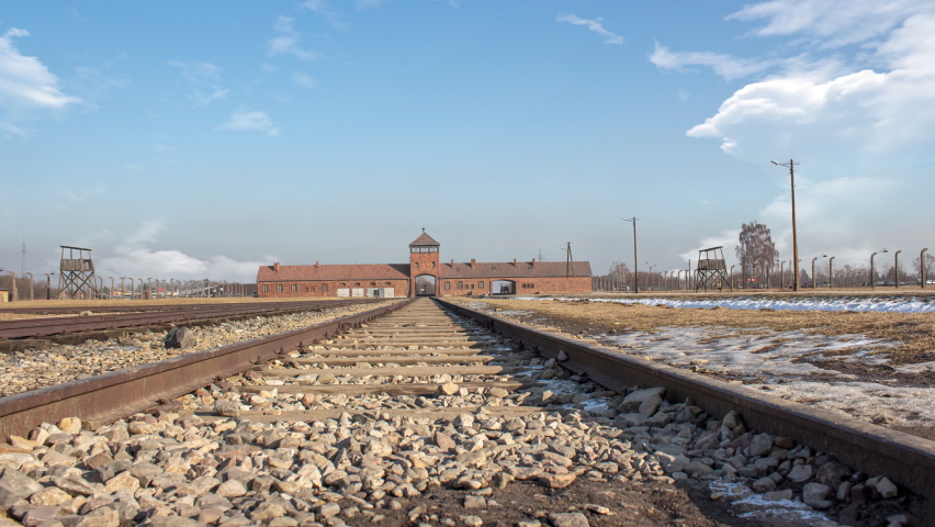 Time lapse of Auschwitz concentration camp in occupied Poland during World War II and the Holocaust. during a sunny cloudy day. There is the  train binary in close up