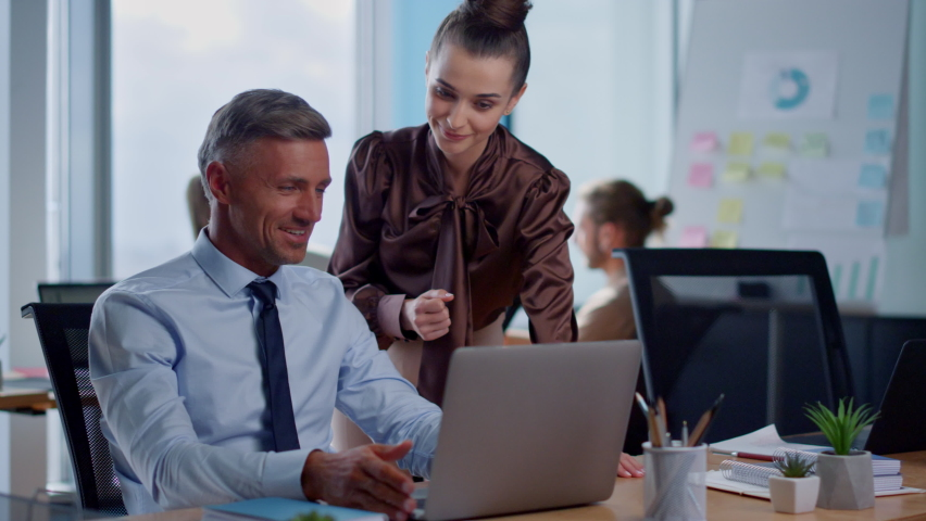 Cheerful business people brainstorming in open space. Male employee showing good results to female colleague on laptop screen. Smiling business man and business woman using laptop | Shutterstock HD Video #1062931501