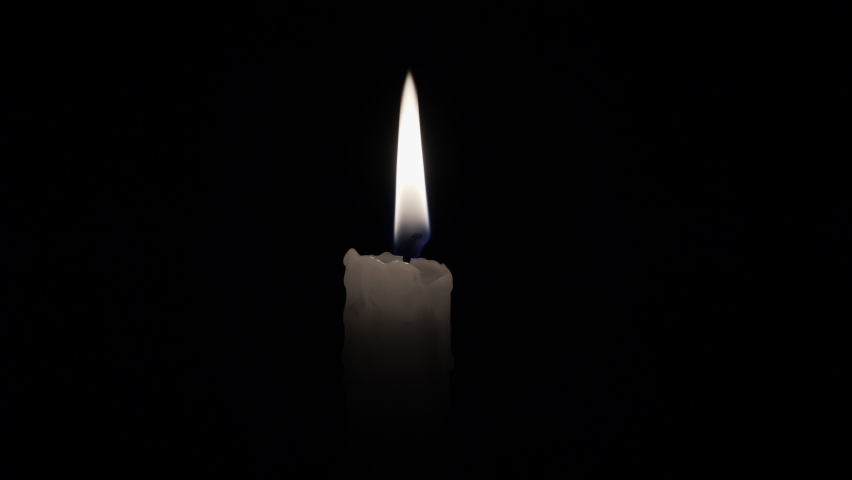 Candle. Match lights the candle wick. Light a candle in the darkness. Flame of a candle lit on a black background. Royalty-Free Stock Footage #1062939166