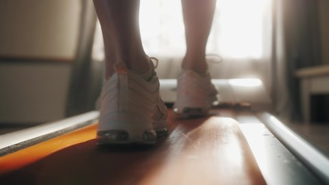 Fitness girl exercising cardio home workout. Person running on treadmill at home.