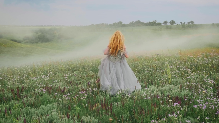 young happy fantasy blonde woman queen runs, walks in green nature, whirls, dances fluttering skirt, gray dress waving in motion. Vintage summer clothes. Candid girl princess bride. Back rear view Royalty-Free Stock Footage #1062950140