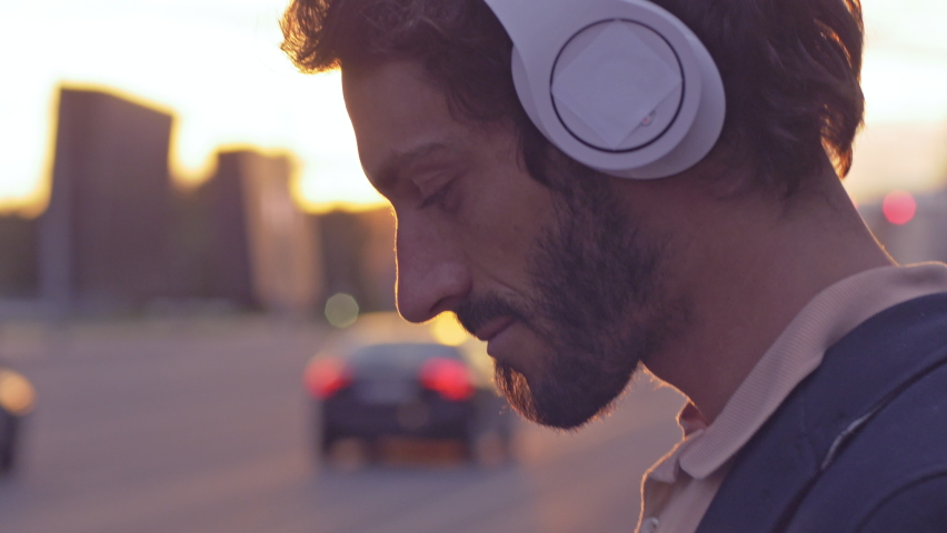 Young man enjoying music on the urban city street. Close-up of smiling male putting headphones on and listening to favorite song at sunset with lens flare. Royalty-Free Stock Footage #1062950554