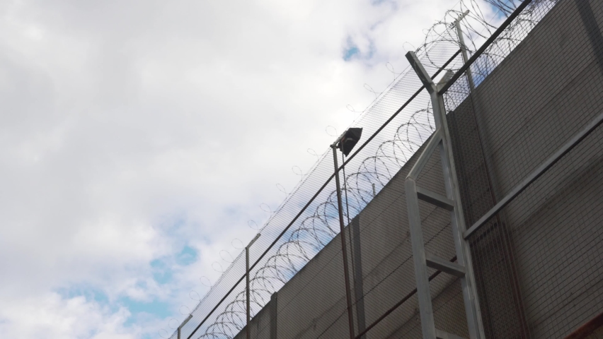 A high fence with barbed wire and spotlights. border fence.