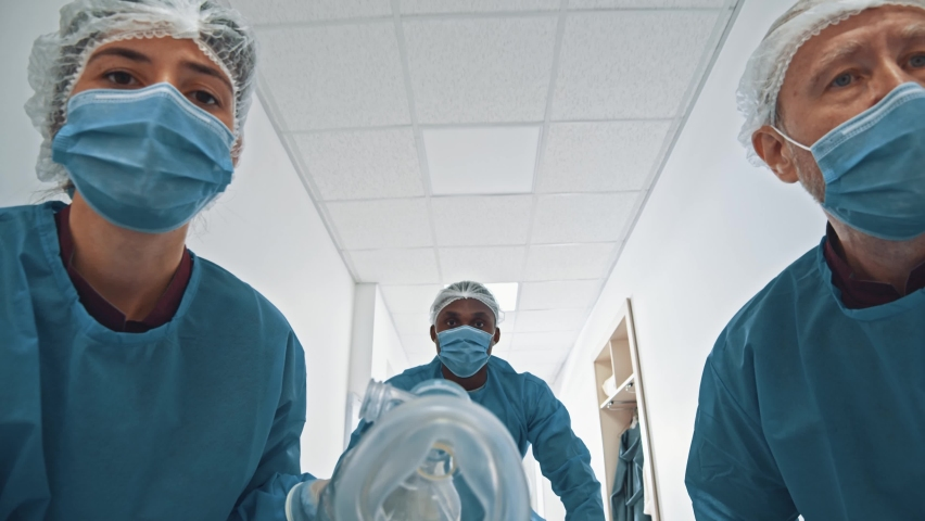 POV shot of patient lying on stretcher bed seeing group of paramedic doctors running through hospital corridor for emergency surgery. Royalty-Free Stock Footage #1062955660