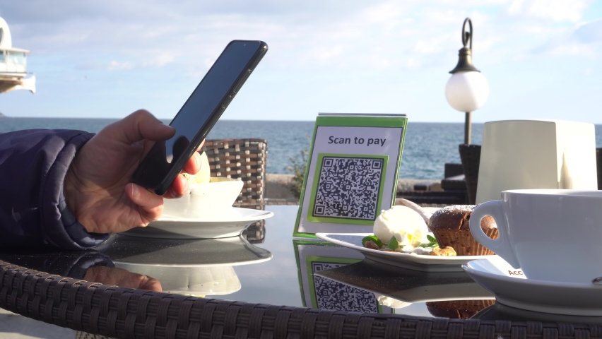 Pay touch-free with a QR code. QR code scanning app. Touchless digital payment option for businesses. A man sits in an open cafe on the beach   Shutterstock HD Video #1062963652