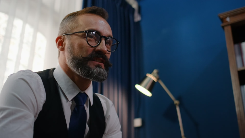 Portrait of Caucasian man with eye glasses talk or conversation with someone in working room of his house. Concept of communication with other people with speaking and face to face.   Shutterstock HD Video #1062964195