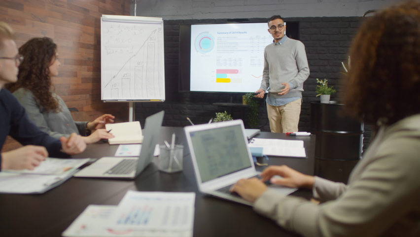 Medium shot of young middle eastern man making presentation to his colleagues using flipchart and projector with charts and diagrams discussing strategy together at modern loft presentation room   Shutterstock HD Video #1062965050