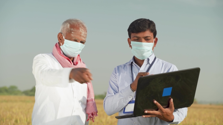 Farmer and banker or corporate government officer discussing on laptop about crop yield, credit and loan subsidy while both worn face mask due to covid-19 coronavirus pandemic   Shutterstock HD Video #1062965065
