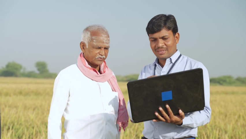 Confused Indian farmer Scratching his head while banker or corporate government officer discussing on laptop about crop yield, credit and loan subsidy at agriculture farmland during hot sunny day   Shutterstock HD Video #1062965071