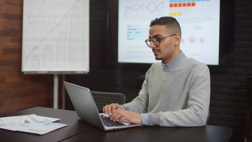 Medium close up of middle eastern specialist working on laptop then smiling at camera in modern open space office with flipchart and projector in background   Shutterstock HD Video #1062965284