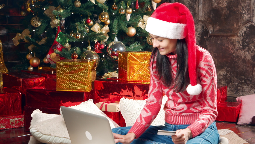 Young happy woman in Santa hat shopping online using laptop and credit card while sitting near Christmas tree. Preparing for the New Year and Christmas.   Shutterstock HD Video #1062966016