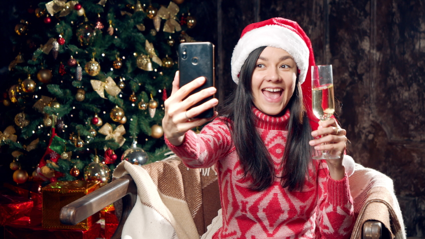 Happy young woman in Santa hat holding a glass of champagne while recording video congratulation or having online communication with friends using smartphone at home.   Shutterstock HD Video #1062966718