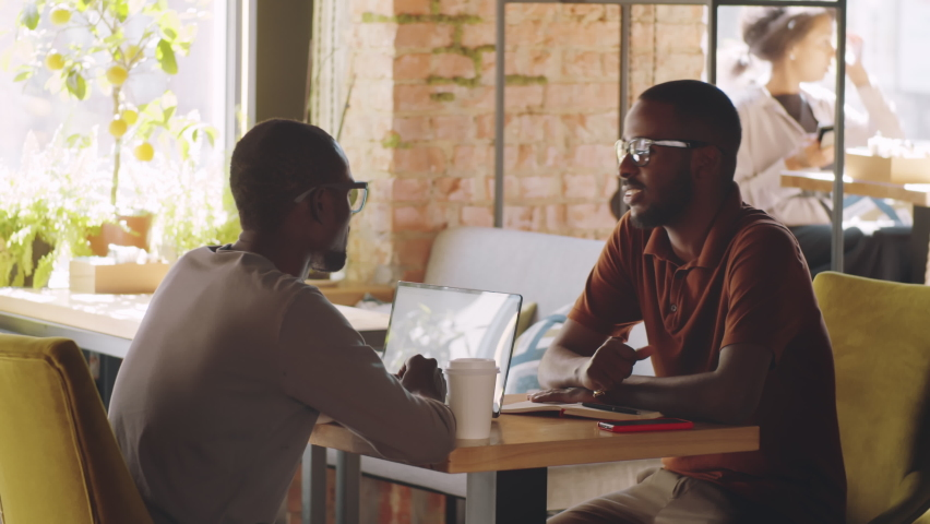 Two Afro-American male colleagues greeting each other with fist bump and chatting while meeting in cafe during business break