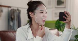 attractive woman wearing facial mask on the sofa talking by the online video recommending her mask and smiling with causual emotion, close up view