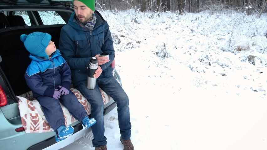 Winter road trip. Father and son sitting inside car trunk in snowy forest, drinking hot tea from thermos and sing a song. Outdoor picnic, family activity on nature in cold season. Royalty-Free Stock Footage #1062979579