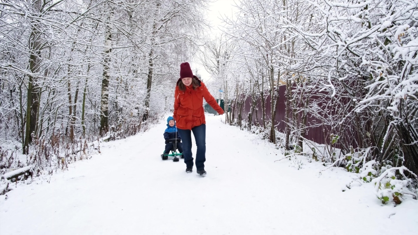 Family winter activity. Mother walks with her little son on snow-covered street. Mom rides child boy on sled on snowy road. Royalty-Free Stock Footage #1062979591