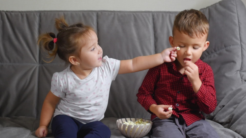 Cute Kids Sitting on the couch feeding each other popcorn very fun   Shutterstock HD Video #1062979834
