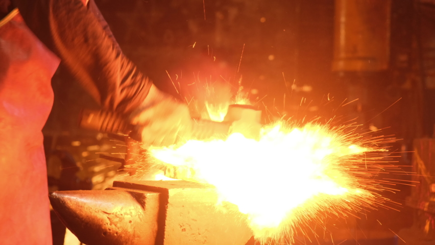 Medium shot of a man with a hammer hitting red-hot metal. A blacksmith works with metal in a forge. Sparks from impacts to metal
