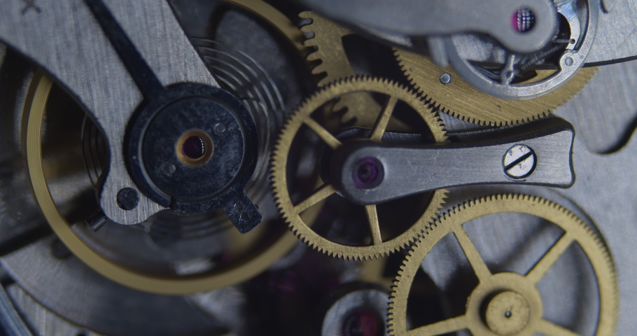 The internal gears and components of an old vintage mechanical stopwatch. Macro close up of mechanical movement, with tick tick tick sound. Royalty-Free Stock Footage #1062993340