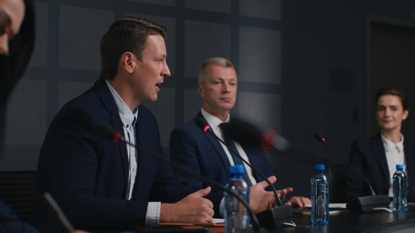Political speaker talks at meeting room of modern business forum. Man in suit discusses partnership at conference in convention hall. Expert group of colleagues working together at official event Royalty-Free Stock Footage #1062994312