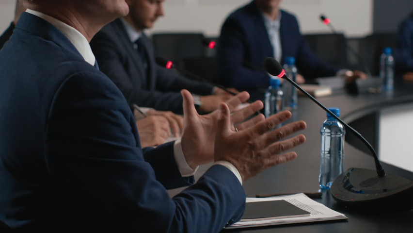 Political speaker talks at meeting room of modern business forum. Adult man in suit discusses partnership at conference in convention hall. Expert group of colleagues works at official event closeup Royalty-Free Stock Footage #1062994330