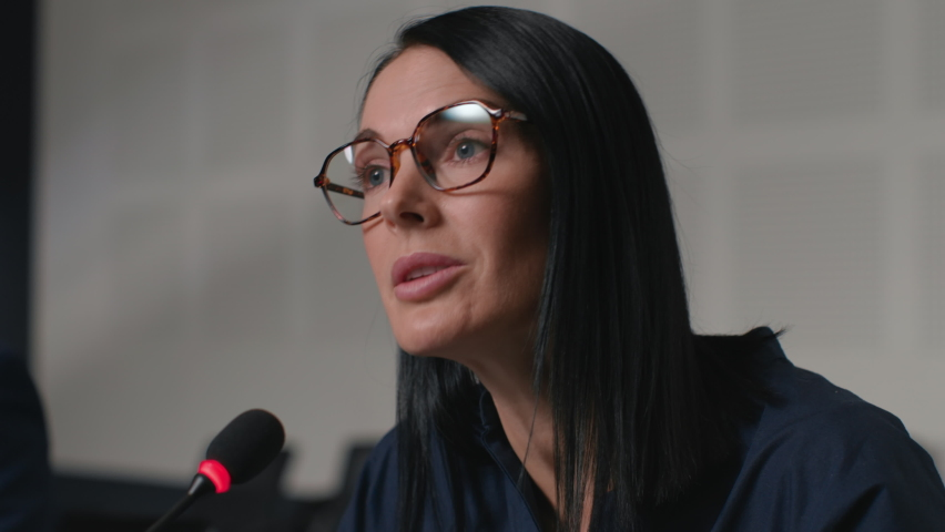 Political speaker talks at meeting room of business forum. Woman in suit discusses partnership at conference in convention hall. Expert group works on important information at official event close-up Royalty-Free Stock Footage #1062994360