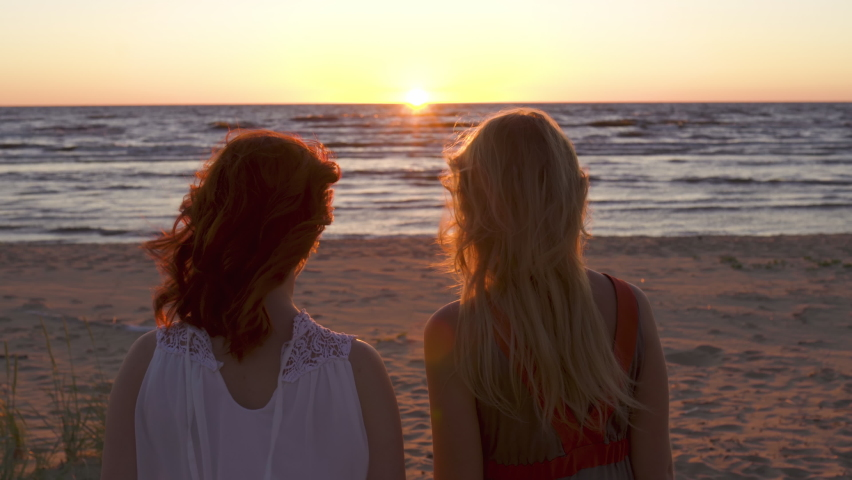 Two young women walk together towards sunset