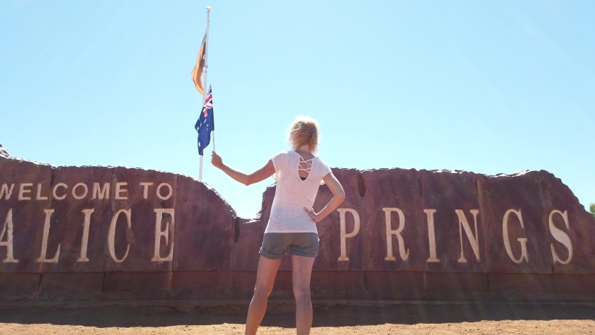 Happy carefree tourist woman at Alice Springs Welcome Sign in Northern Territory, Central Australia. Tourism in Outback Red Center desert. Travel discovery road in Australian trip in dry summer season | Shutterstock HD Video #1063007500