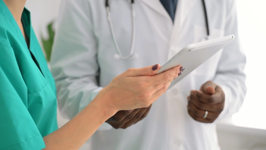 Closeup view of man and woman doctors using tablet during working day at clinic spbas. African American person and his female colleagues use electronic device and work together while standing indoors Royalty-Free Stock Footage #1063014154
