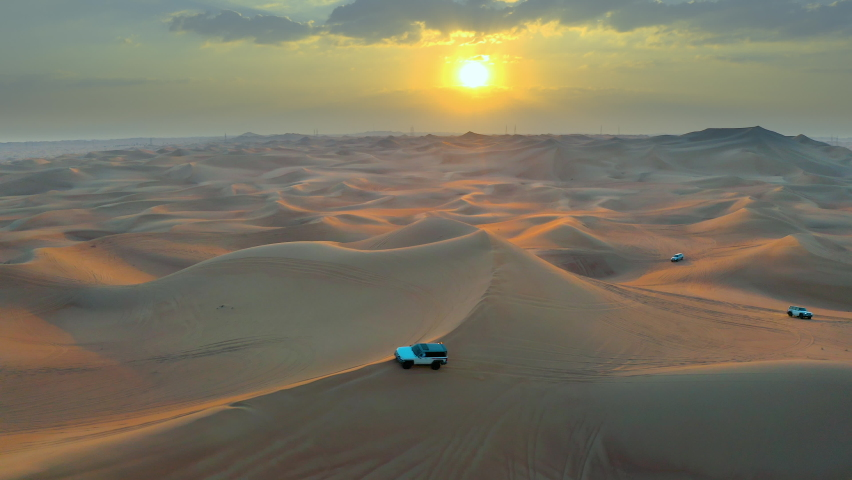 Desert Safari off-road with sunset view. car vehicle rides on desert dune barkhan or sand-dune. Aerial drone view. | Shutterstock HD Video #1063024036