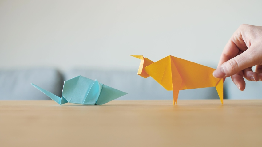 An Origami Rat and Ox meet on table. Zodiac animals change for Chinese new year. The cow is the Chinese zodiac sign for 2021 and mouse for 2020. Animals made by hand by traditional paper folding. 4K.