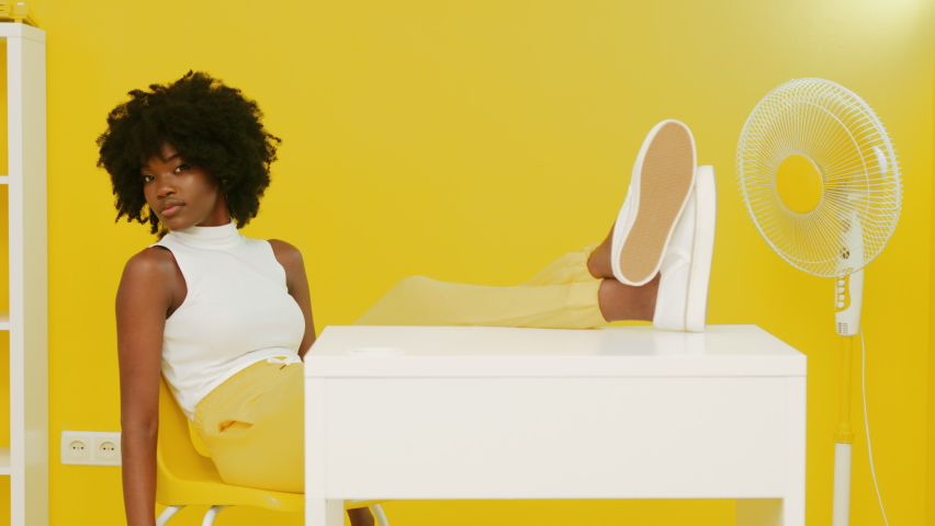 Portrait of stylish African woman with black curly hair, looking at camera, sitting at desk in yellow room, holding legs on table, fan on pedestal is on, creative space, Slow motion. Royalty-Free Stock Footage #1063047607