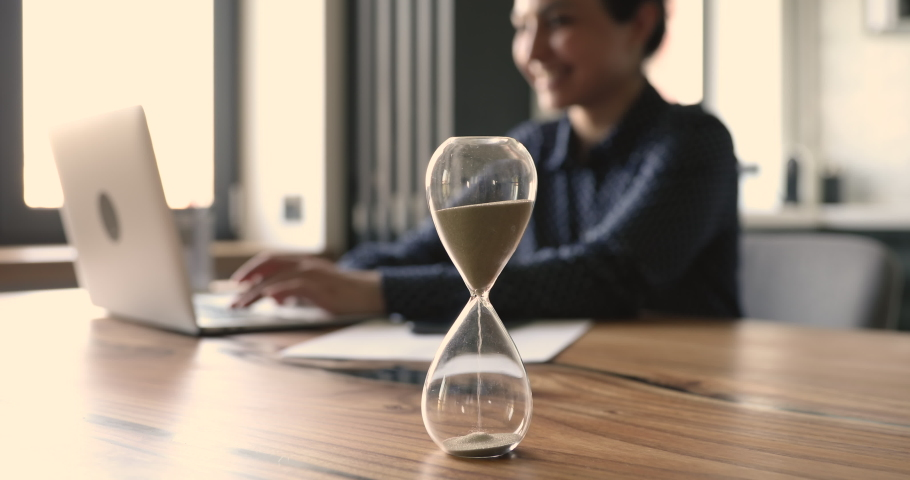 Close up focus on sandy hourglass with smiling indian businesswoman working on computer on background. Time management, working office hours, punctuality compliance deadlines schedule concept. Royalty-Free Stock Footage #1063053895