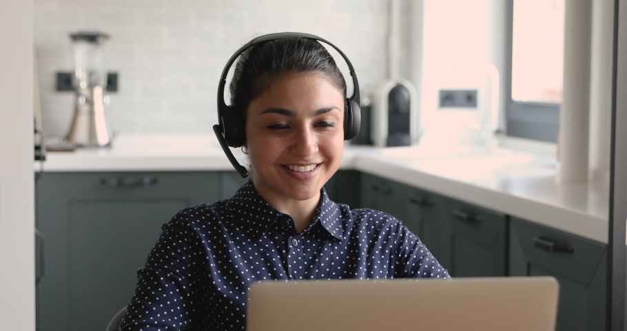 Attractive pleasant young mixed race indian woman in wireless headset with microphone holding video call conversation with client or colleagues, discussing working issues or studying on online courses Royalty-Free Stock Footage #1063053928