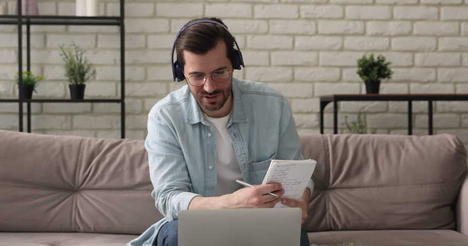 Interested young european handsome man in glasses studying distantly, holding video call consultation with tutor at home, learning foreign language, making notes in copybook, online education concept