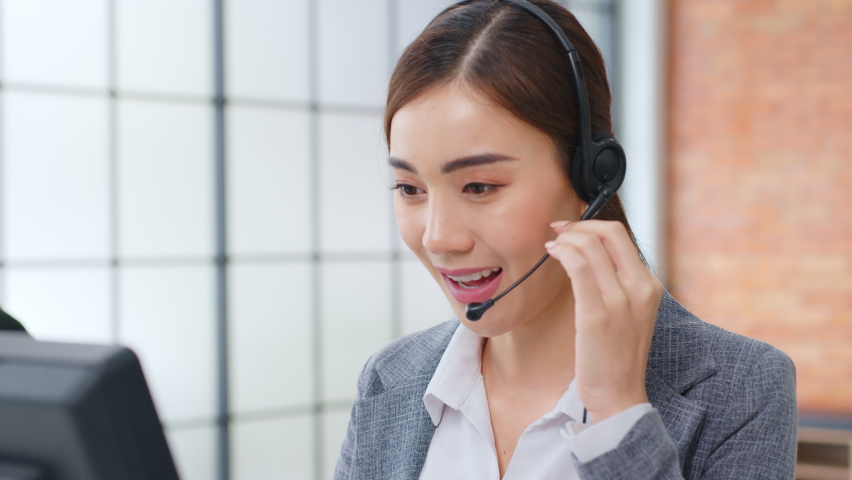 Closeup Asian woman call center, customer service, telesales in formal suit wearing headset or headphone talking with customer in modern office