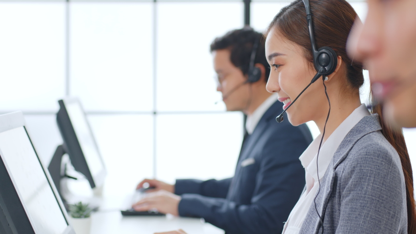 Asian call center team, customer service, telesales in formal suit wearing headset or headphone talking with customer in modern office