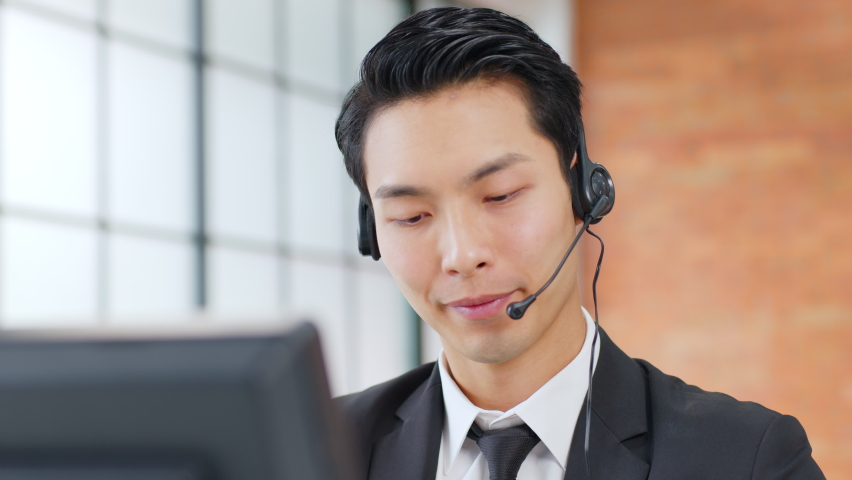 Closeup Asian man call center, customer service, telesales in formal suit wearing headset or headphone talking with customer in modern office