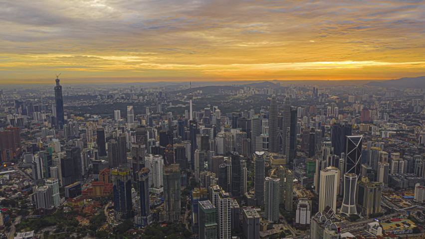 Time lapse: Beautiful and dramatic golden hour view of the Kuala Lumpur skyline overlooking the national landmarks,  the Petronas Towers and Kuala Lumpur Tower. Golden hour.  | Shutterstock HD Video #1063063330
