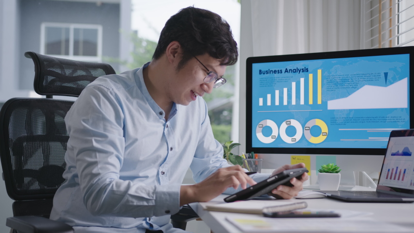 Young attractive asian thai man busy work multiple screen computer or smart tablet on table desk at home in freelance data analyst, data science scientist for business. Royalty-Free Stock Footage #1063085524