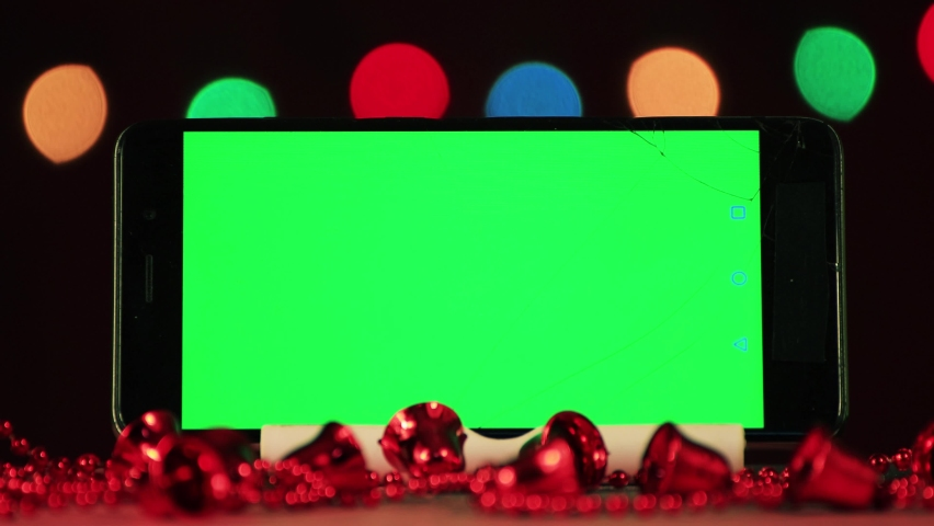 Black phone close-up with green screen for insertion. Red beads are out of focus ahead. In the background, Christmas colored lights glow in the dark at night. New year greeting card. 4K. Royalty-Free Stock Footage #1063093750