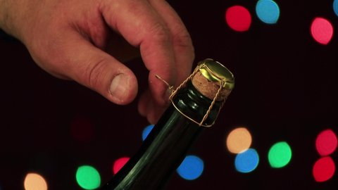 Male hand open a bottle of Christmas champagne close-up. First, unscrew the wire, then remove the plug. A festive night and a solemn moment came. New Year colored lights on a black background. 4K.