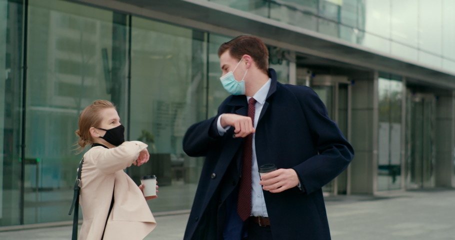 Young Business People in Masks Meet with Elbow Bump Greeting near Office Building. Man and Woman Keep Social Distance at COVID-19 Coronavirus Pandemic. Slow Motion Orbit Gimball Shot Royalty-Free Stock Footage #1063097107