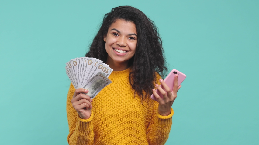 Surprised young african american woman 20s in yellow sweater isolated on blue background studio. People lifestyle concept. Using mobile cell phone hold fan of cash money in dollar banknotes say wow Royalty-Free Stock Footage #1063109299